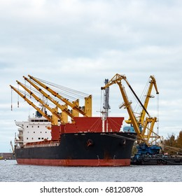 Black cargo ship loading in the port of Riga, Europe