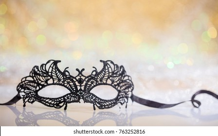 Black carnival mask on white surface, abstract bokeh background