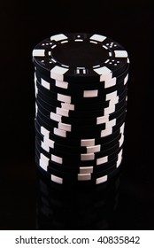 Black casino chips on black background
