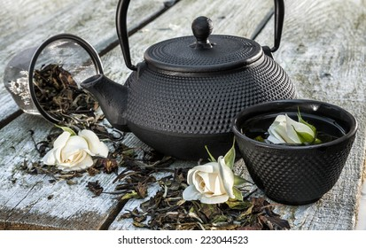 Black cast iron teapot and cup with rose on old wooden table.