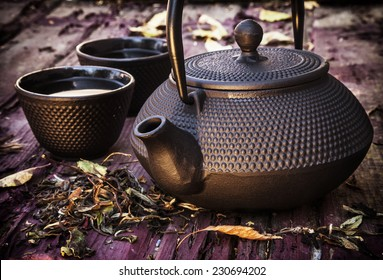 Black cast iron teapot and cup on old wooden table.