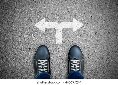 Black casual shoes standing at the crossroad making decision which way to go - two ways to choose