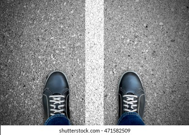 Black casual shoes standing over the white line that separate left and right. Standing on both side. Right and wrong. Good and bad.