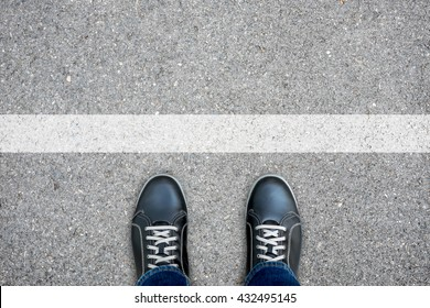 Black casual shoes standing at the white line making decision - stop and turn back or across the line and go further