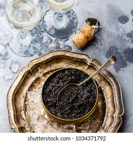 Black caviar in can on ice and champagne on concrete background close-up