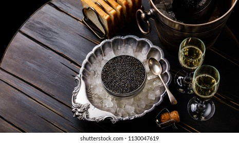 Black caviar in can on ice in silver bowl, bread and champagne in ice bucket on black wooden background
