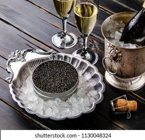 Black caviar in can on ice in silver bowl and champagne on black wooden background