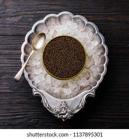 Black caviar in can on ice in silver bowl on black wooden background