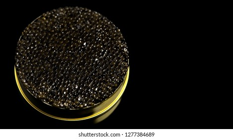 Black Caviar isolated on black background. High quality real natural sturgeon black caviar close-up. Delicatessen. Texture of expensive luxury caviar in tin can. Seafood.