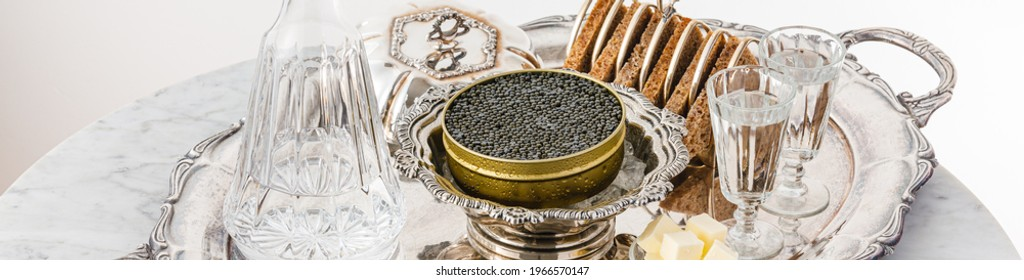 Black caviar on ice in silver bowl, Vodka and bread on white marble table