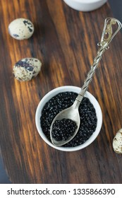 Black caviar with quail eggs over wooden board.