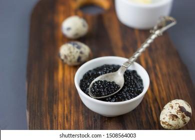 Black caviar with quail eggs over wooden board
