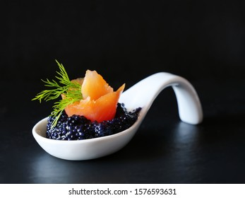 Black caviar with smoked salmon bite in white porcelain spoon over black background.
