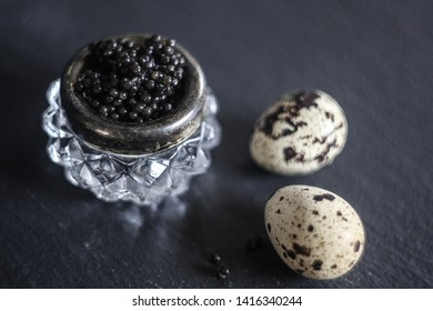 Black caviar in a vintage glass jar with quail eggs on a black stone board. It can be used for food and cooking magazines; healthy lifestyle books; for interior and print design