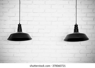 Black ceiling lamps vector. Two black ceiling lamps, light between and iluminated wall texture.