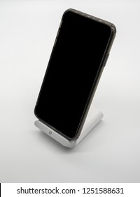 Black cellphone charging on modern designed wireless charger stand isolated on white bakcground.