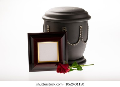 black cemetery urn with blank brown mourning frame on bright background for obituary card