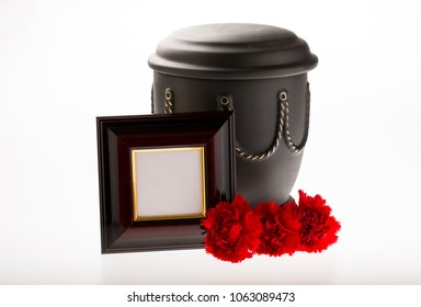 black cemetery urn with blank brown mourning frame and red carnations on bright background for obituary card
