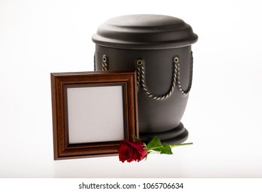 black cemetery urn with blank brown mourning frame and red rose on bright background for obituary card
