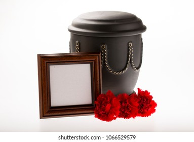 black cemetery urn with blank brown mourning frame carnation flowers on bright background for obituary card