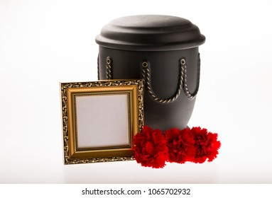 black cemetery urn with blank gold mourning frame and carnations flowers on bright background for obituary card