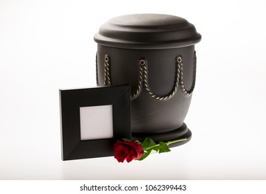 black cemetery urn with blank black mourning frame on bright background for obituary card