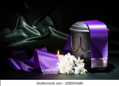 black cemetery urn with candle chrysanthemum and purple tape on green background