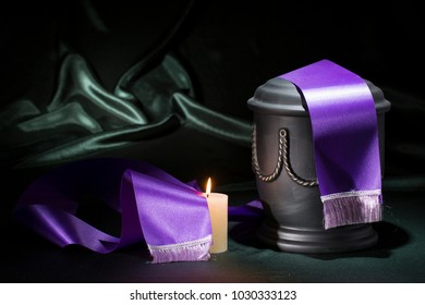 black cemetery urn with candle and purple tape on green background