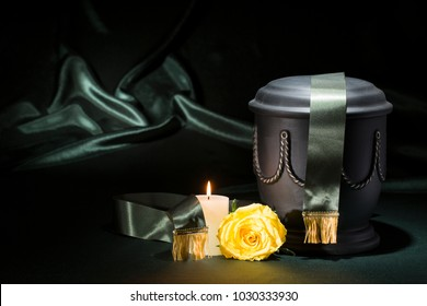 black cemetery urn with candle rose green ribbon on dark green background