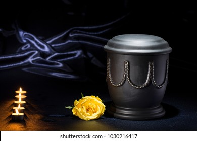 black cemetery urn with candles and yellow rose