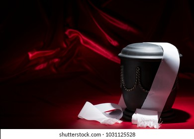 black cemetery urn with with golden decoration and white ribbon on deep red background
