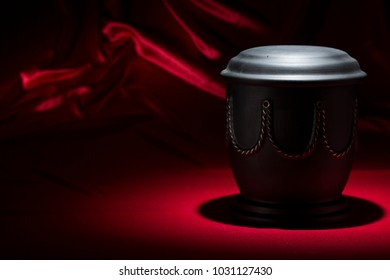 black cemetery urn with with golden decoration on deep red background