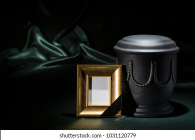 black cemetery urn with golden mourning frame for sympathy card on deep green background