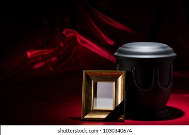 black cemetery urn with golden picture frame for sympathy card