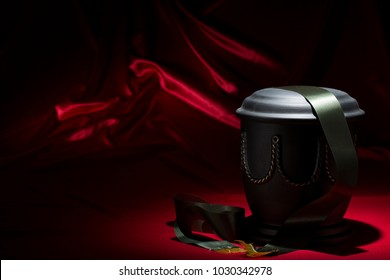 black cemetery urn with green ribbon on red background