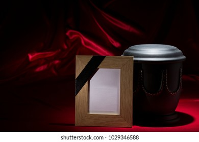 black cemetery urn with mourning frame for sympathy card on deep red background