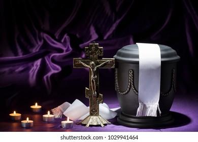 black cemetery urn with Orthodox cross on dark background