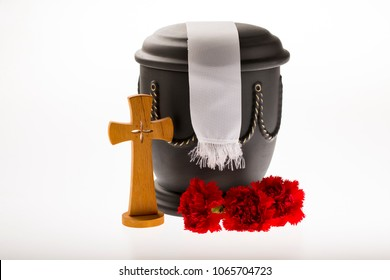 black cemetery urn with red carnation, catholician cross, and white ribbon on bright background for funeral card
