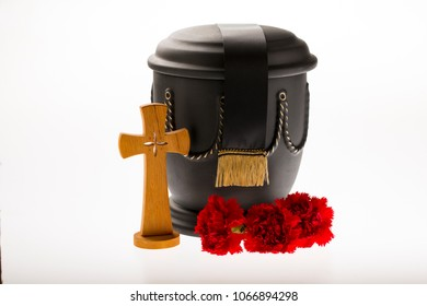 black cemetery urn with red carnation flowers catholician cross, and black ribbon on bright background for funeral card