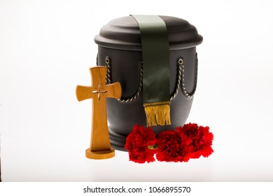black cemetery urn with red carnation, catholician cross, and green ribbon on bright background forobituary card
