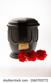 black cemetery urn with red carnations and black ribbon on bright background for sympathy card