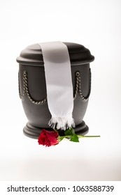 black cemetery urn with red rose and white ribbon on bright background for obituary card