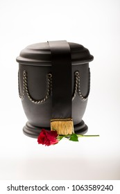 black cemetery urn with red rose and black ribbon on bright background for obituary card