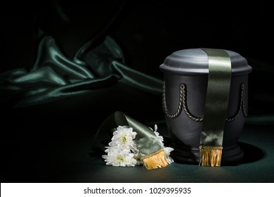Black cemetery urn with white chrysanthemum and green tape