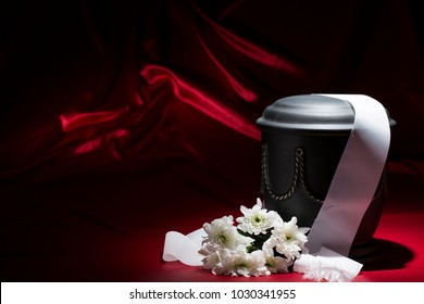 black cemetery urn with white chrysanthemum and white ribbon on deep red background