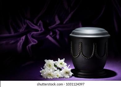 black cemetery urn with white chrysanthemum on deep purple background