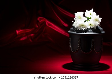 black cemetery urn with white chrysanthemum on deep red background