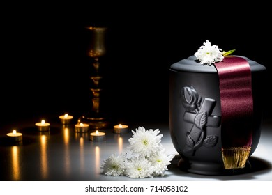 black cemetery urn with white chrysanthemum on dark background