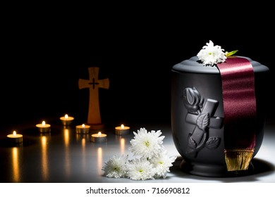 black cemetery urn with white chrysanthemum with red tape