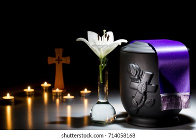 black cemetery urn with white lilly flower cross, and pink tape